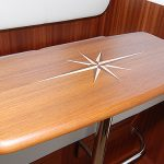 Beautiful teak pilothouse table with an inlaid compass star.