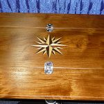Compass rose inlay on teak folding table.
