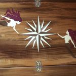 Dining table inlaid design of mermaids around a compass rose.