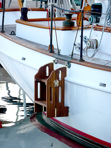 A four-step teak boat ladder with standoff legs.