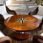 Specially cut teak deck table with inlaid compass rose and teak foot.