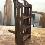 Finished eight-step teak boarding ladder with standoff leg.