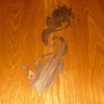 Inlaid design of two seahorses on a teak dining table.