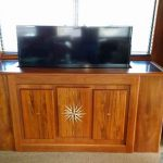 Teak entertainment center for a yacht that features an inlaid compass rose.